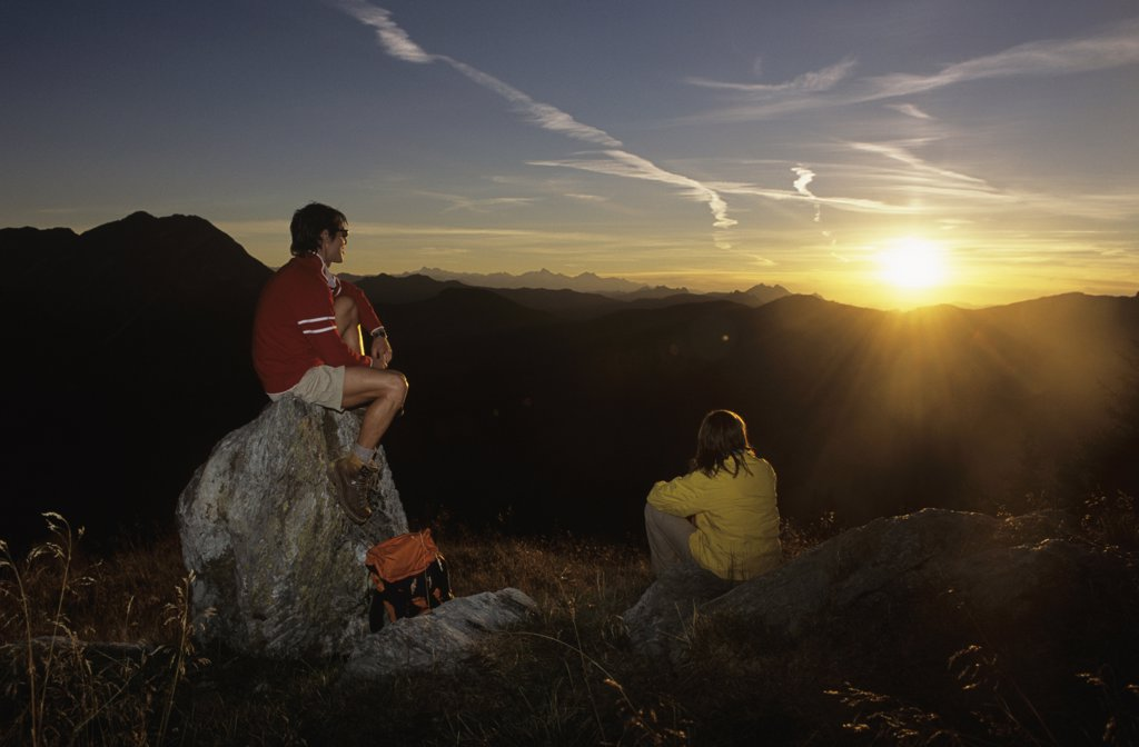 Couple watching sunset in mountains : Stock Photo