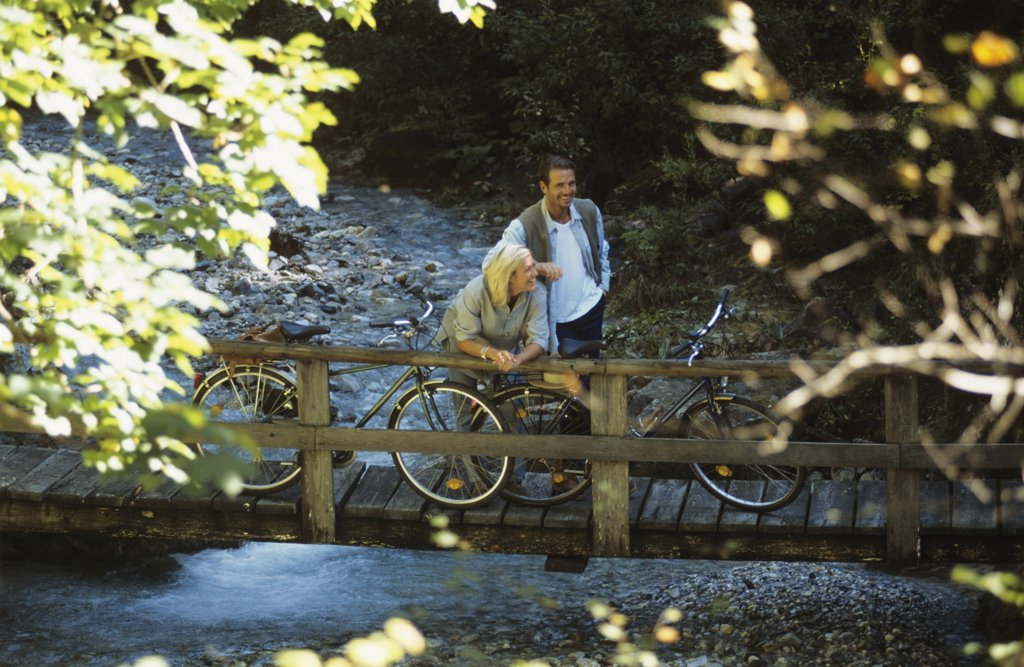 Couple with bicycles, standing on wooden bridge, smiling : Stock Photo