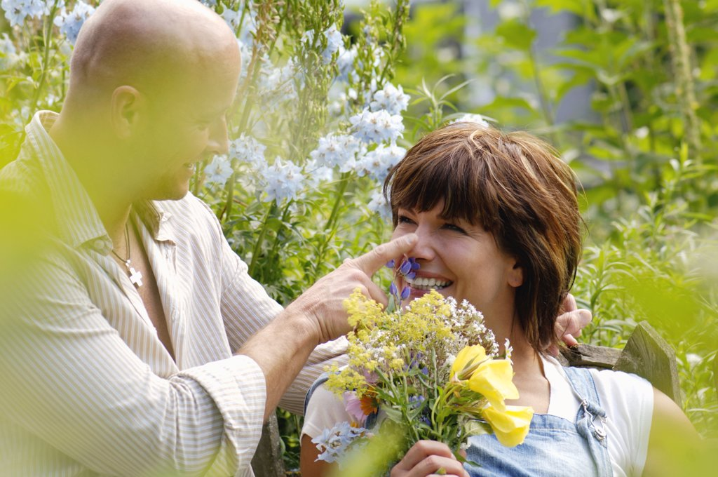 Stock Photo: 1815R-18510 Couple in garden, woman holding bunch of flowers