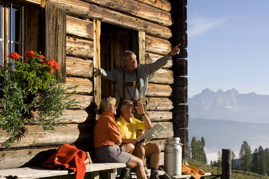 Stock Photo: 1815R-18669 Mature couple sitting in front of mountain hut, farmer pointing