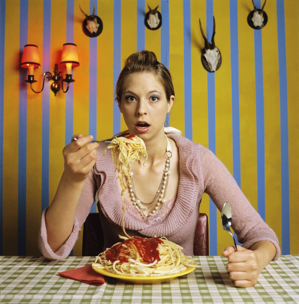 Stock Photo: 1815R-19526 Young woman eating spaghetti