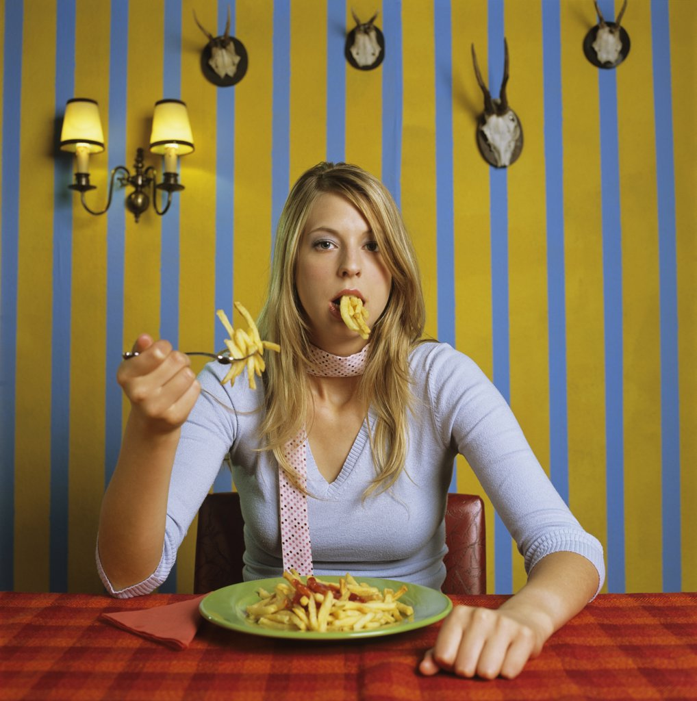 Young woman eating french fries : Stock Photo