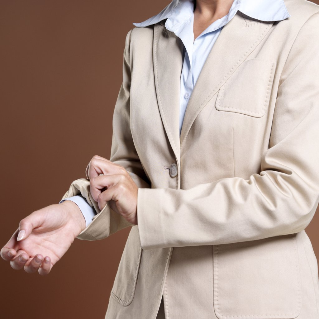 Stock Photo: 1815R-19605 Businesswoman, close-up, rolling up sleeves
