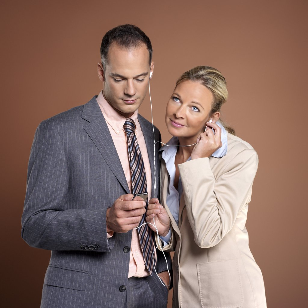 Businessman and businesswoman listening to mp3 player : Stock Photo
