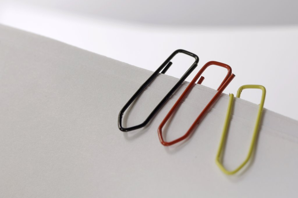 Three paperclips in German national colours : Stock Photo