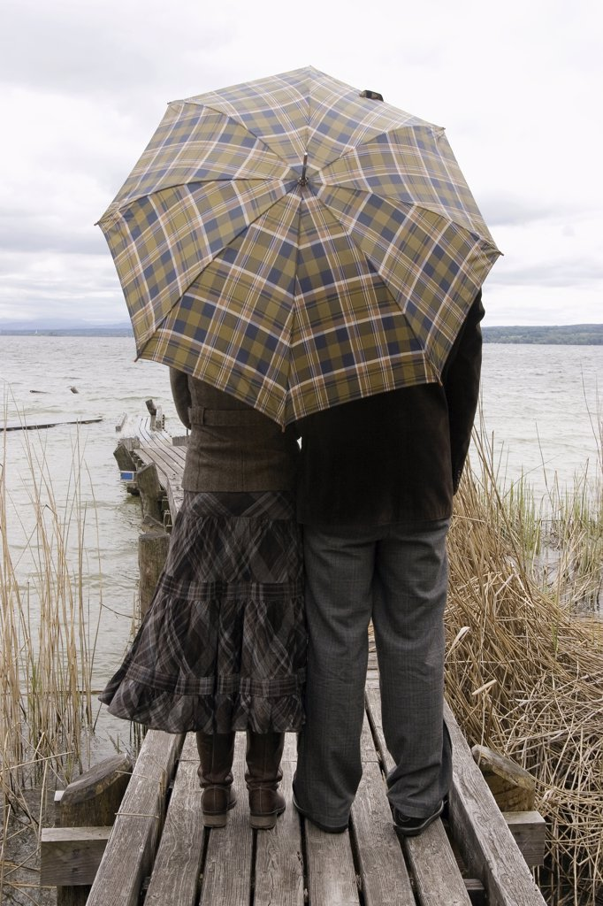 Stock Photo: 1815R-20882 Couple on jetty with umbrella, rear view