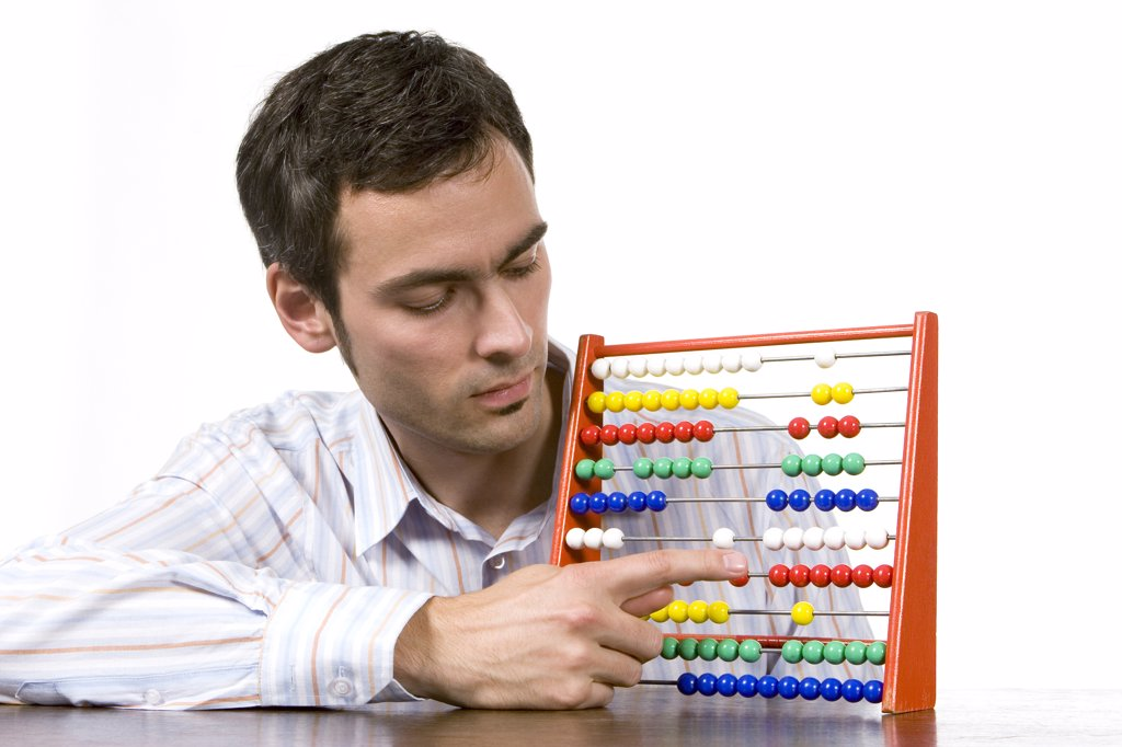 Stock Photo: 1815R-20968 Young man working with abacus