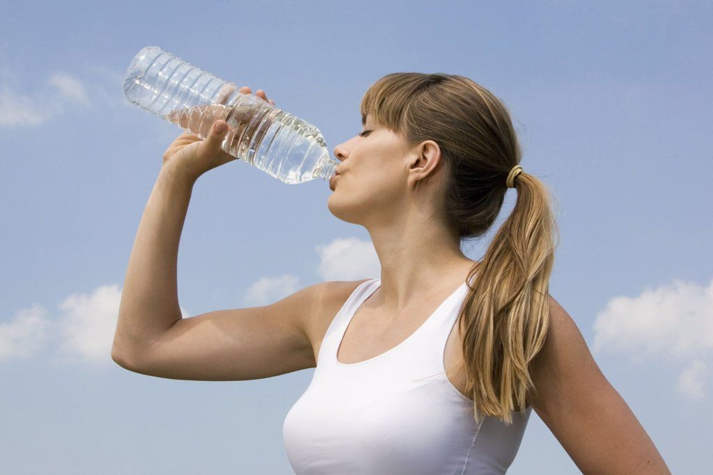Young woman drinking water, portrait : Stock Photo