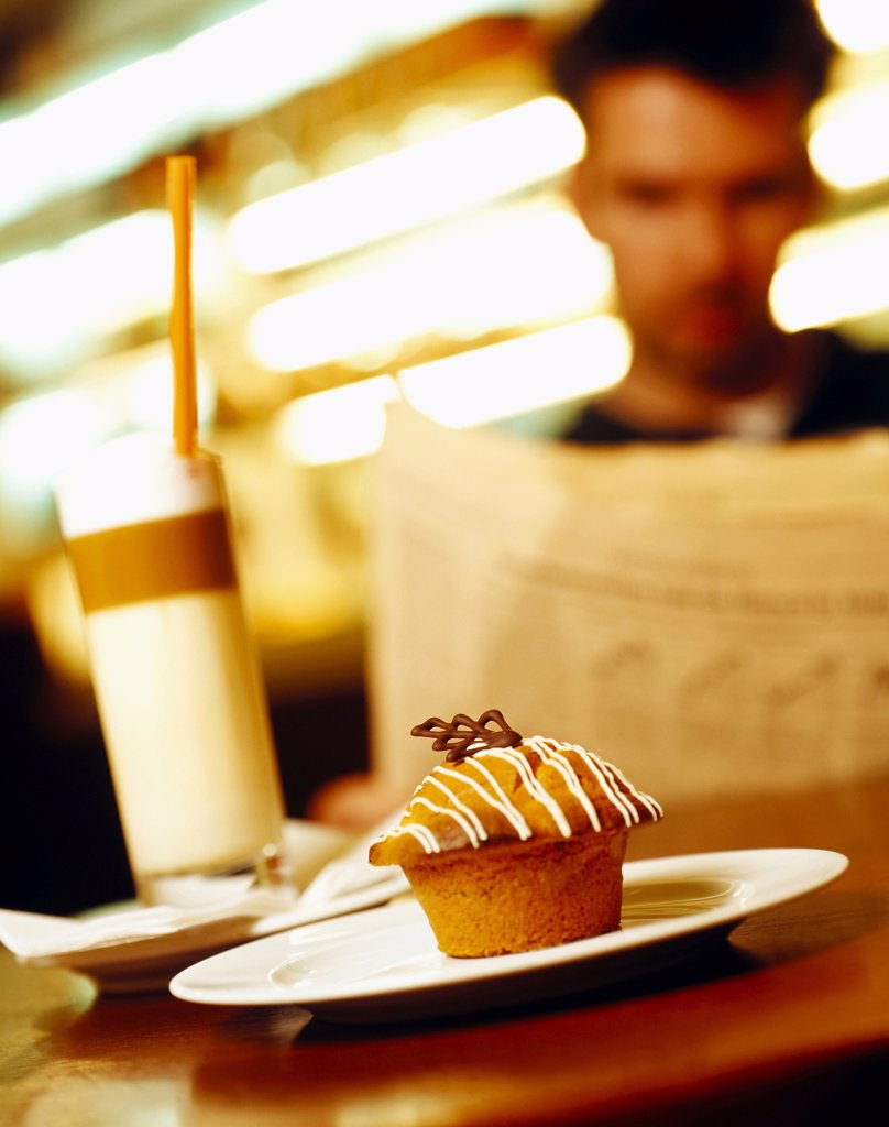 Muffin on plate, person holding paper in background : Stock Photo