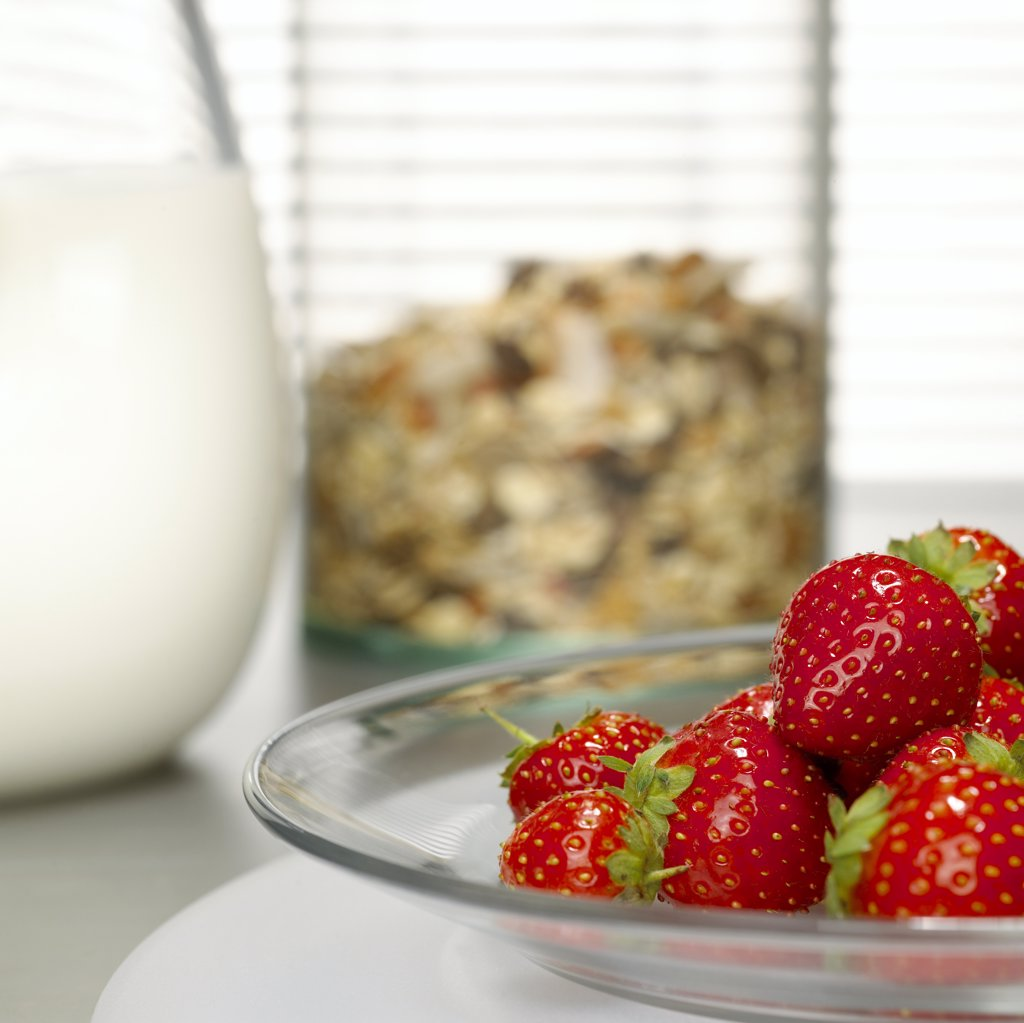Strawberries on plate, cereals and milk in background : Stock Photo