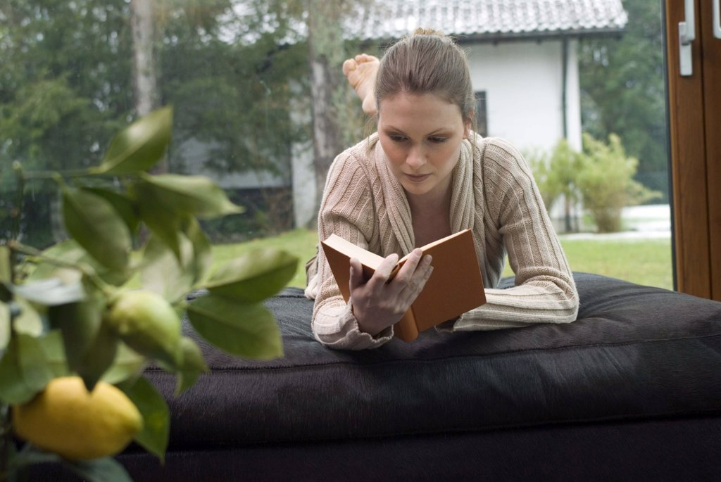 Young woman relaxing on sofa reading a book : Stock Photo
