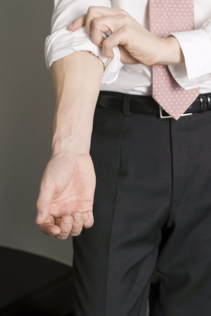 Man rolling up his sleeves : Stock Photo