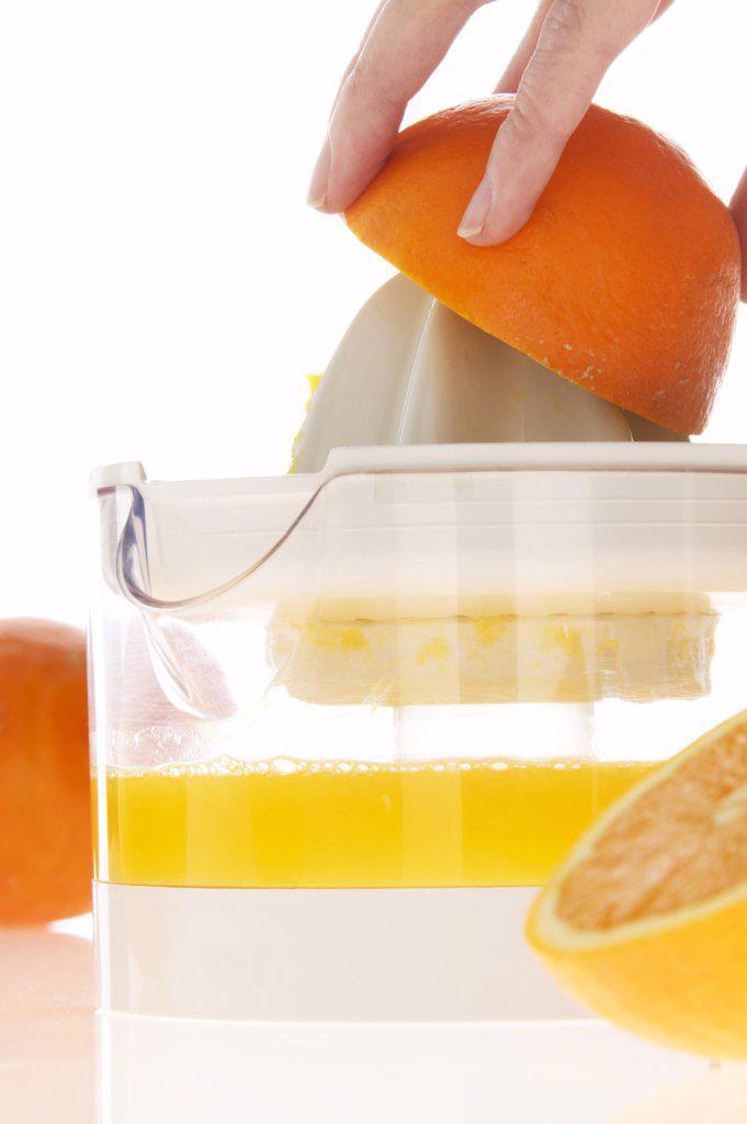 Woman preparing orange juice on juicer, close-up : Stock Photo