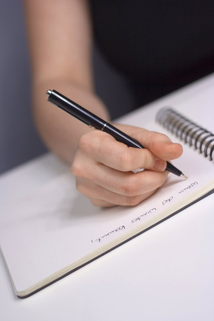 Stock Photo: 1815R-23476 Woman writing in notebook