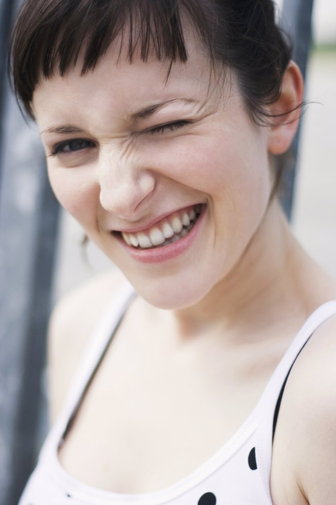 Young woman winking eye, close-up, portrait : Stock Photo