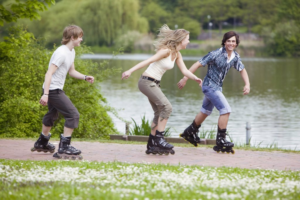 Teenagers inline skating, smiling : Stock Photo