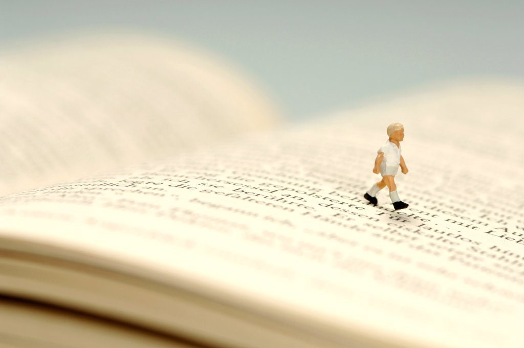 Child walking over book, figurine : Stock Photo