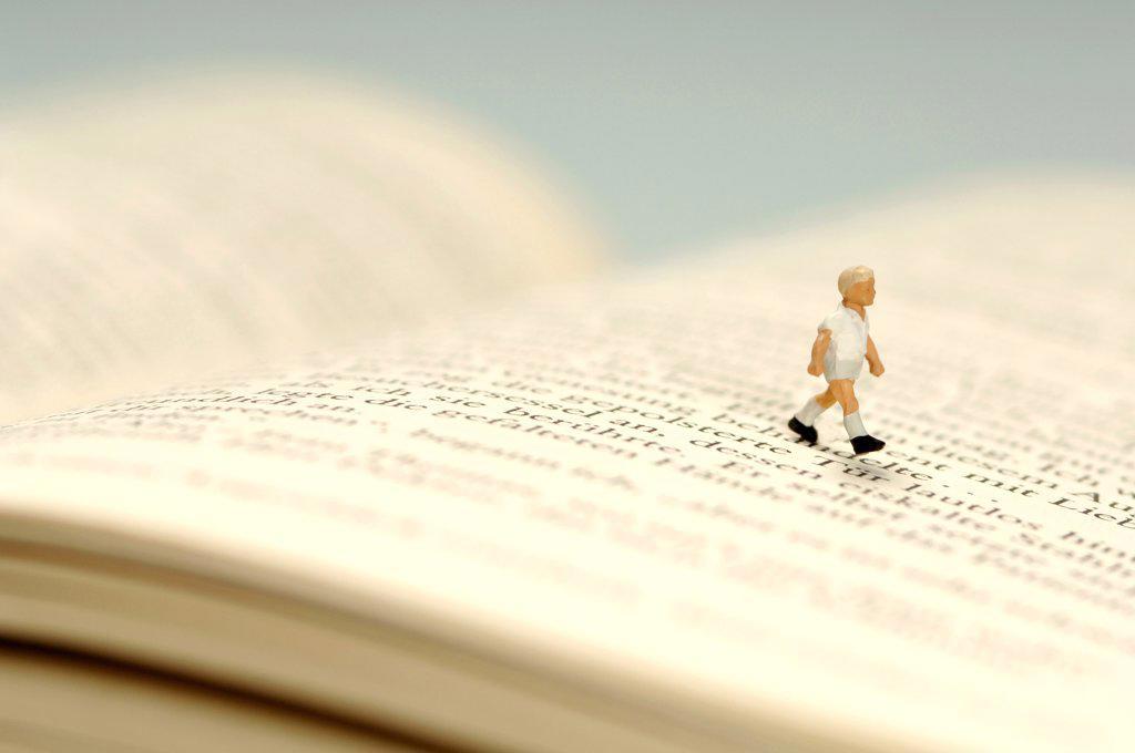 Stock Photo: 1815R-2379 Child walking over book, figurine