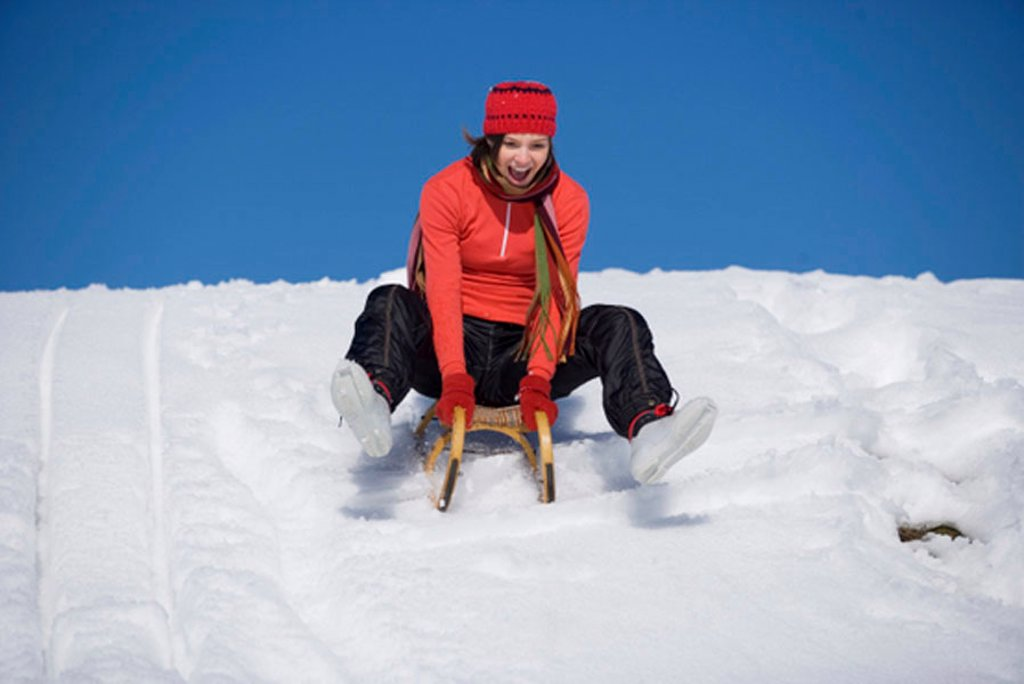 Stock Photo: 1815R-24796 Woman riding on sledge, laughing, low angle view