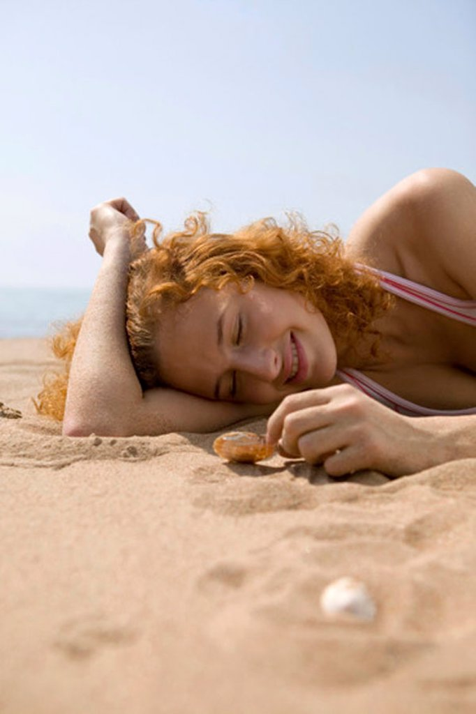 Young woman lying in sand, playing with shell : Stock Photo