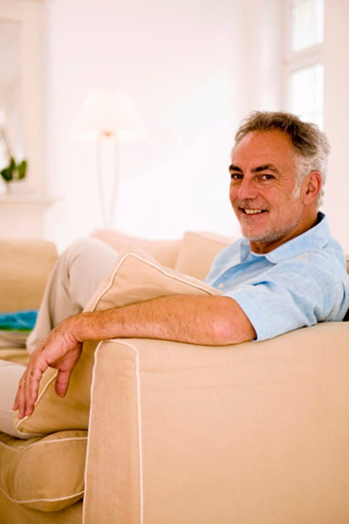Mature man sitting on sofa in living room, portrait, close-up : Stock Photo