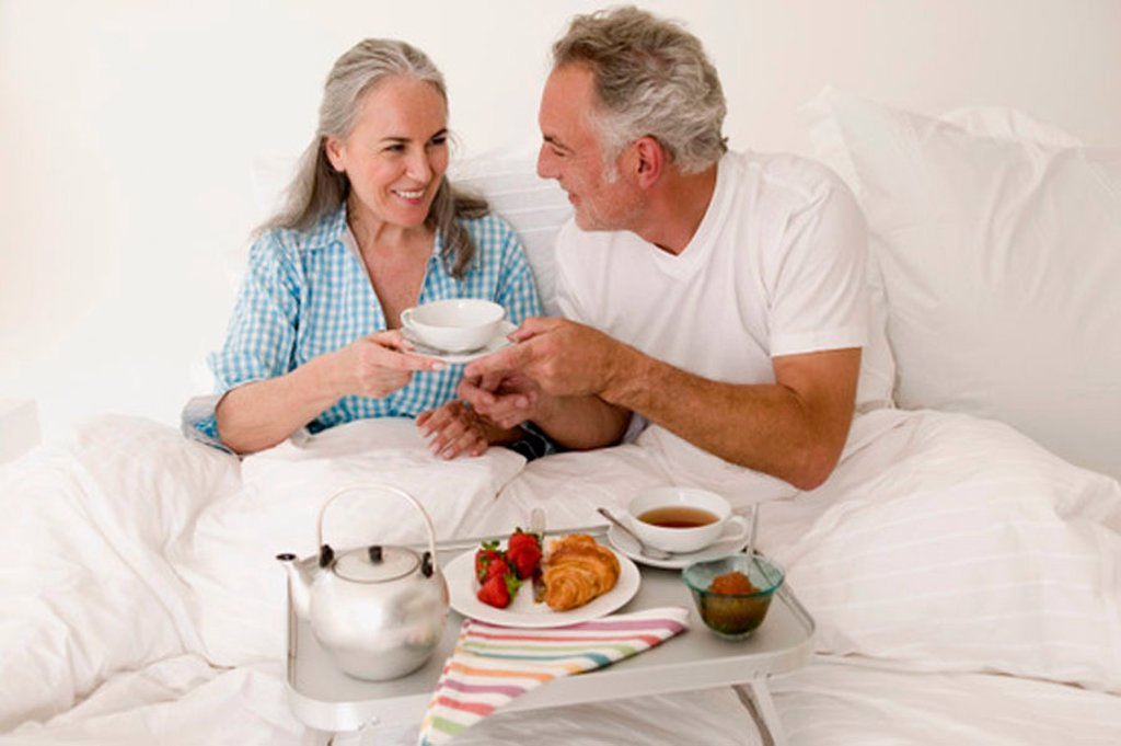 Stock Photo: 1815R-25846 Mature couple sitting on bed with breakfast, smiling