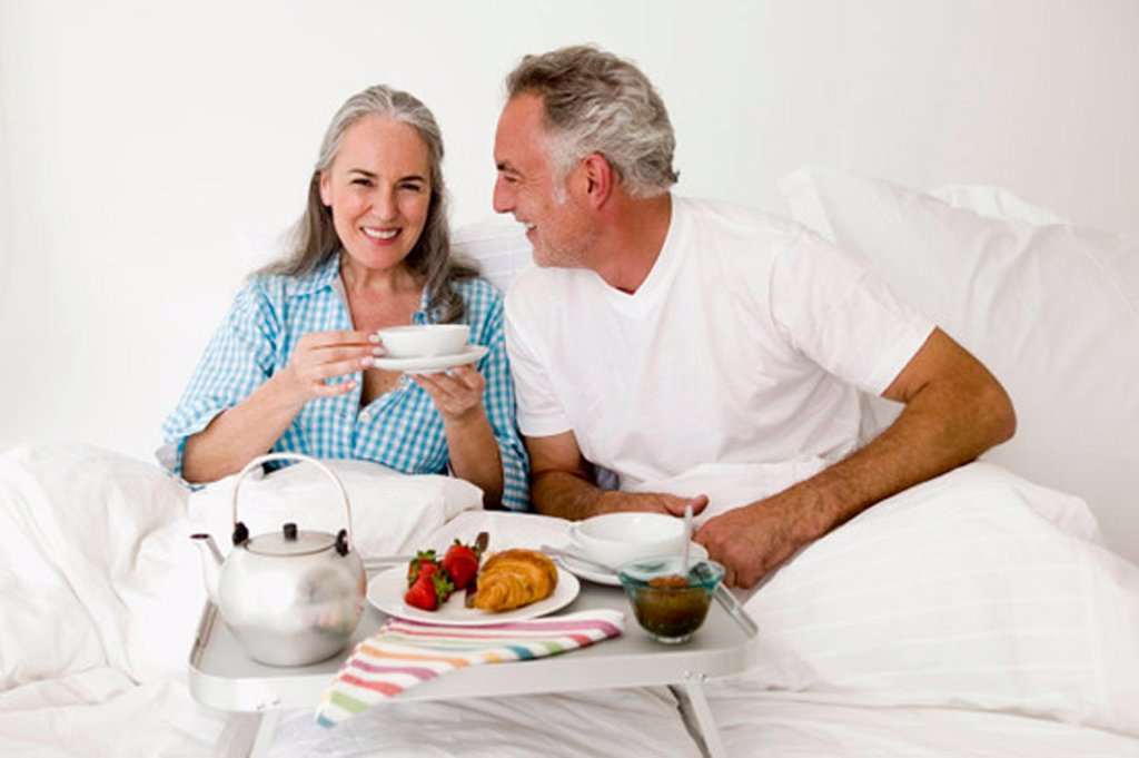 Stock Photo: 1815R-25847 Mature couple sitting on bed with breakfast, smiling