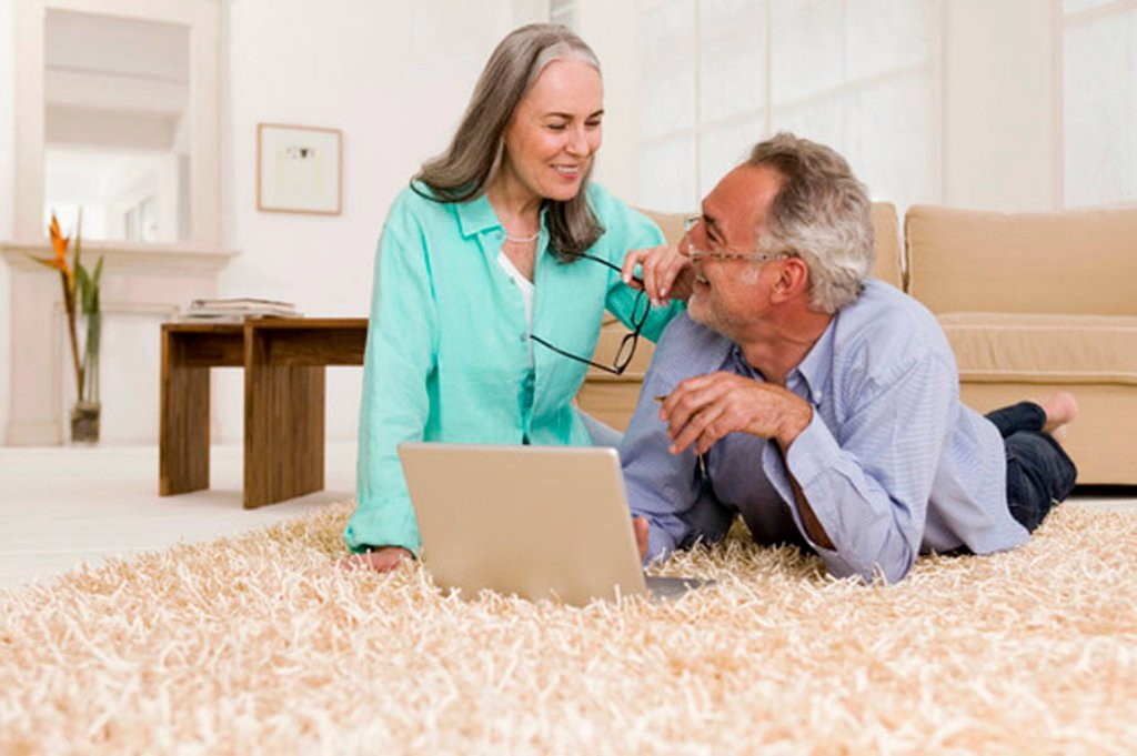 Mature couple lying on carpet with laptop, smiling : Stock Photo