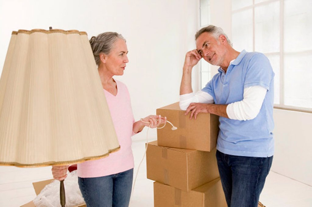 Mature couple in living room with cardboard boxes, discussing : Stock Photo