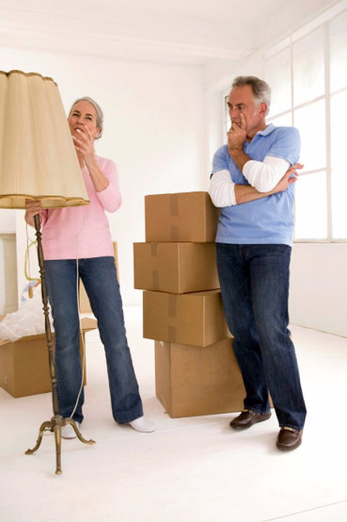 Stock Photo: 1815R-25880 Mature couple in living room with cardboard boxes, thinking