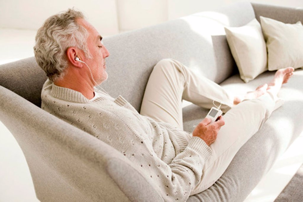 Mature man listening to MP3 player, elevated view : Stock Photo