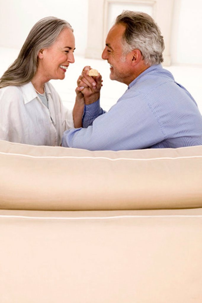 Mature couple sitting on sofa, smiling, side view : Stock Photo