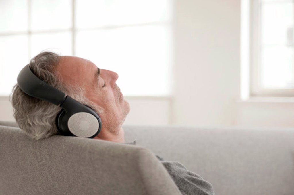 Mature man wearing headphones, eyes closed : Stock Photo