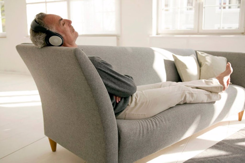 Mature man wearing headphones, sitting on sofa, eyes closed : Stock Photo