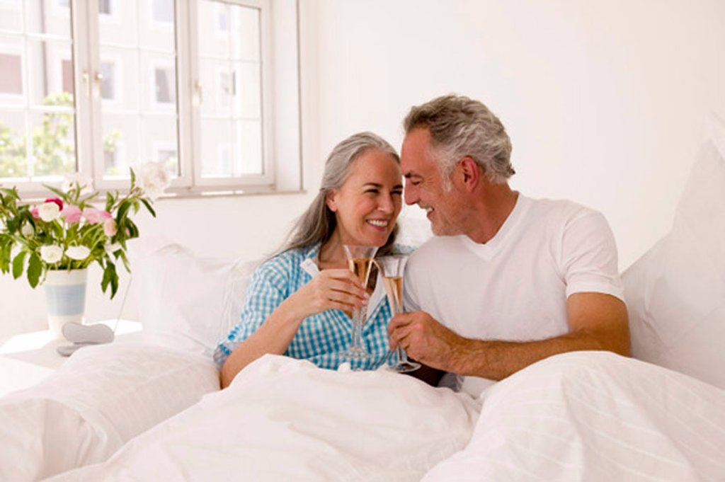 Mature couple on bed toasting champagne, smiling : Stock Photo