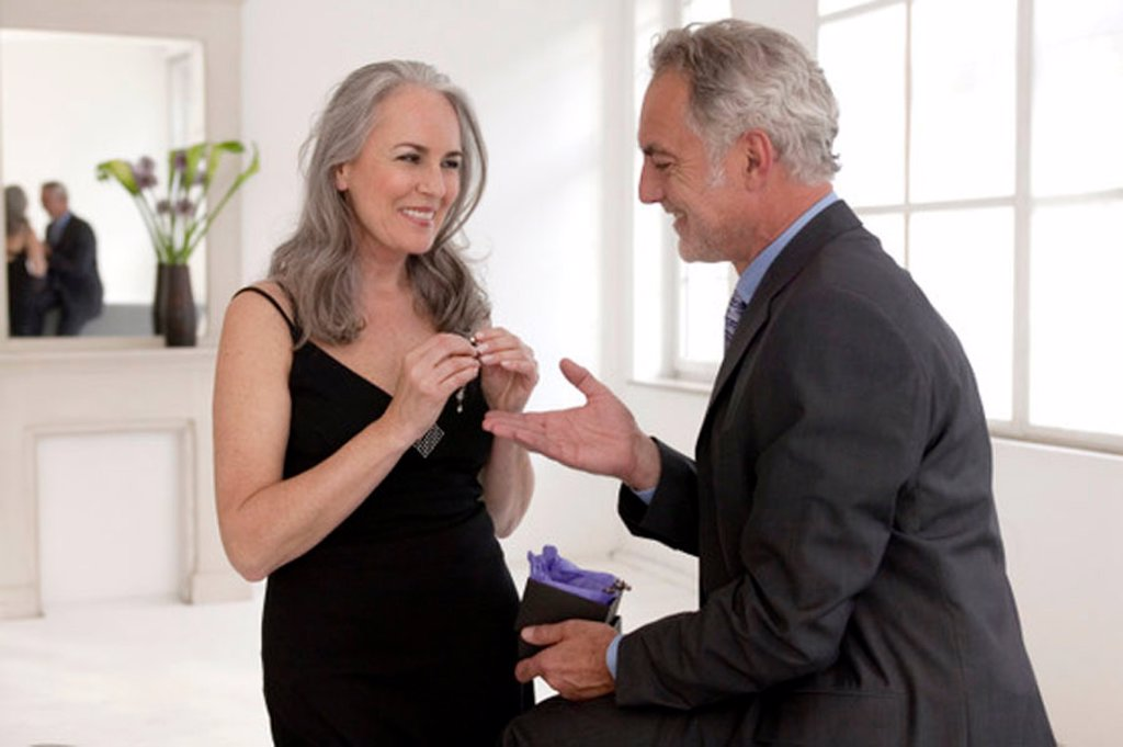 Mature men presenting gift to women, smiling : Stock Photo
