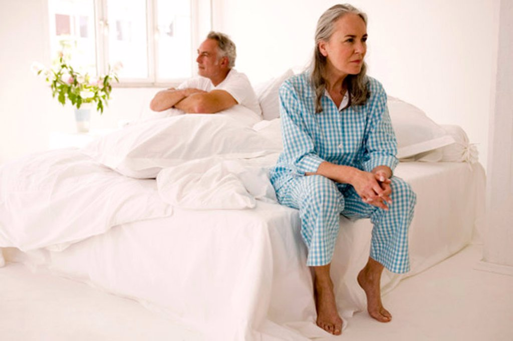 Mature couple sitting on bed (focus on woman in foreground) : Stock Photo