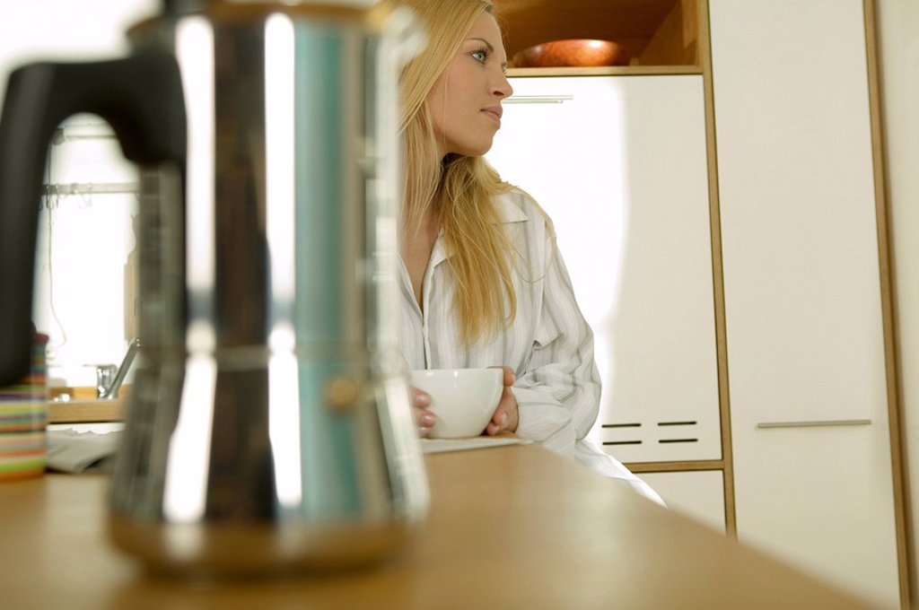 Stock Photo: 1815R-26019 Young woman sitting in kitchen with cup of coffee, looking away