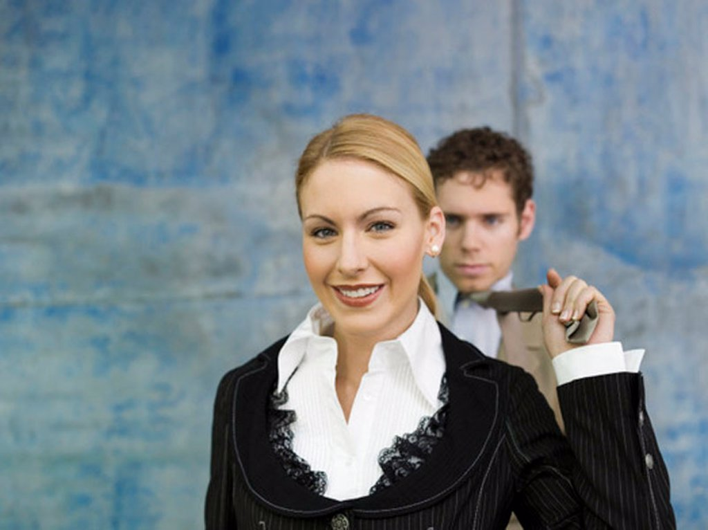 Businesswoman pulling businessman´s tie, smiling : Stock Photo