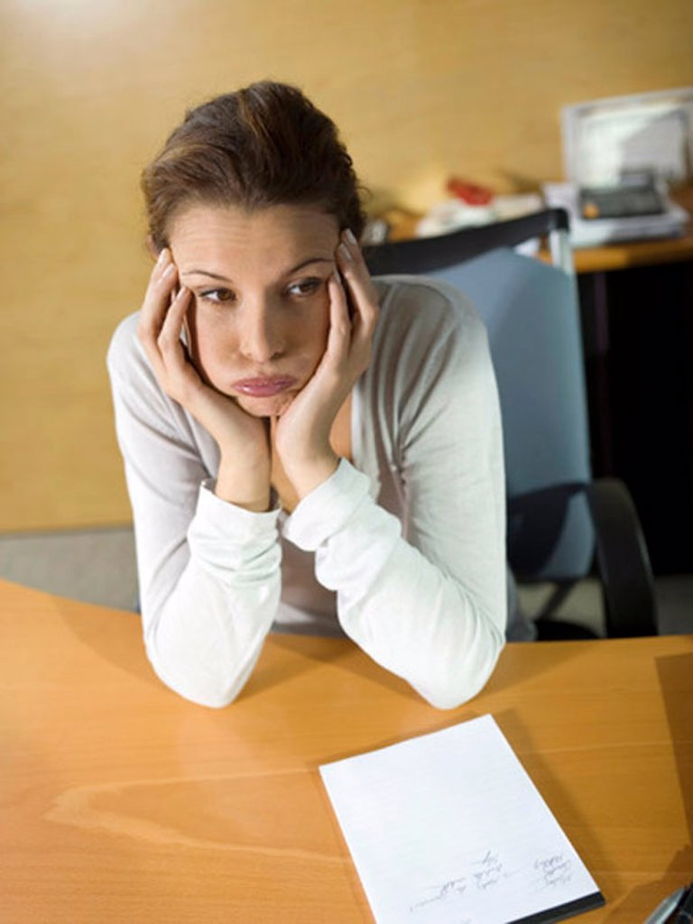 Tired woman sitting at desk, head in hands, close-up : Stock Photo