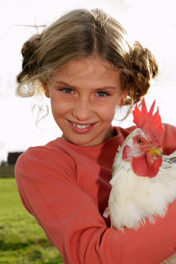 Stock Photo: 1815R-26784 Girl (7-9) holding cock, portrait, close-up
