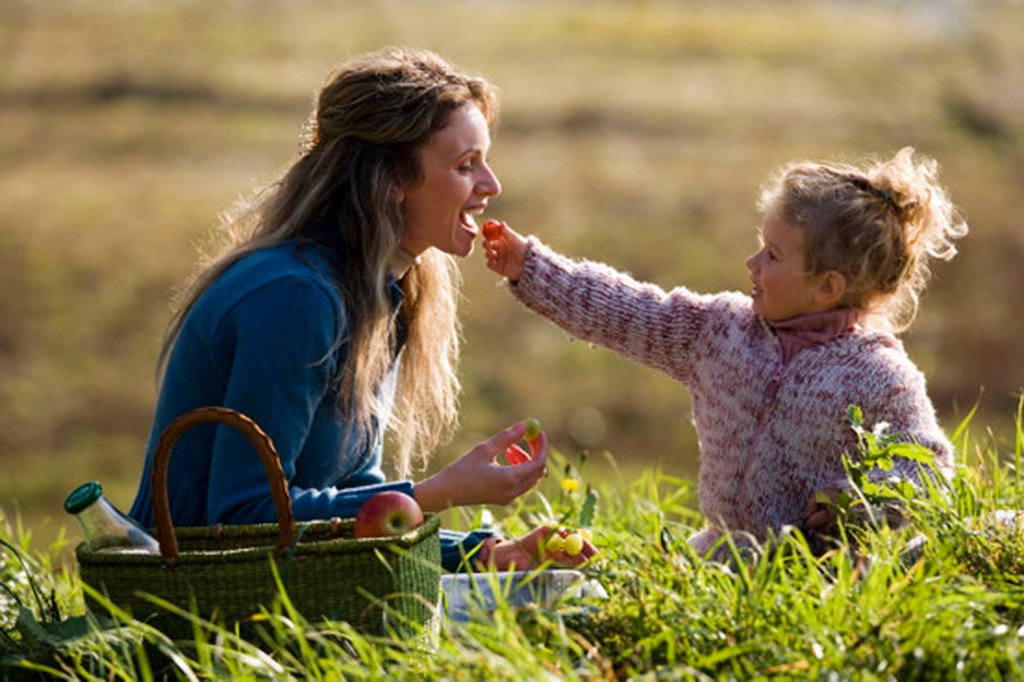 Daughter feeding mother, side view : Stock Photo