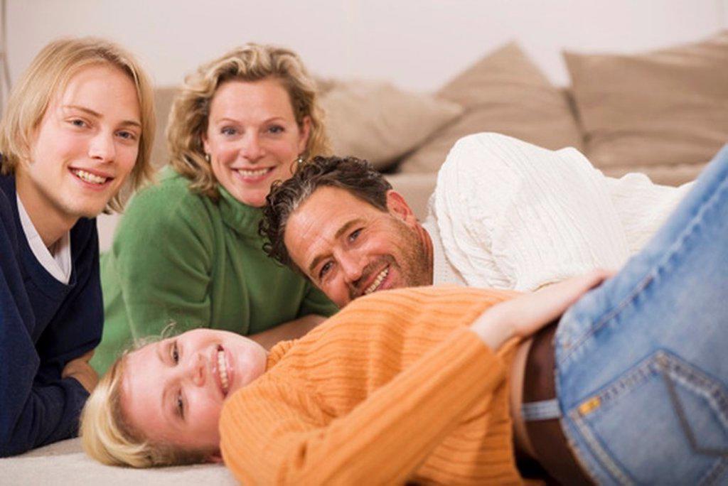 Family lying on floor in living room : Stock Photo