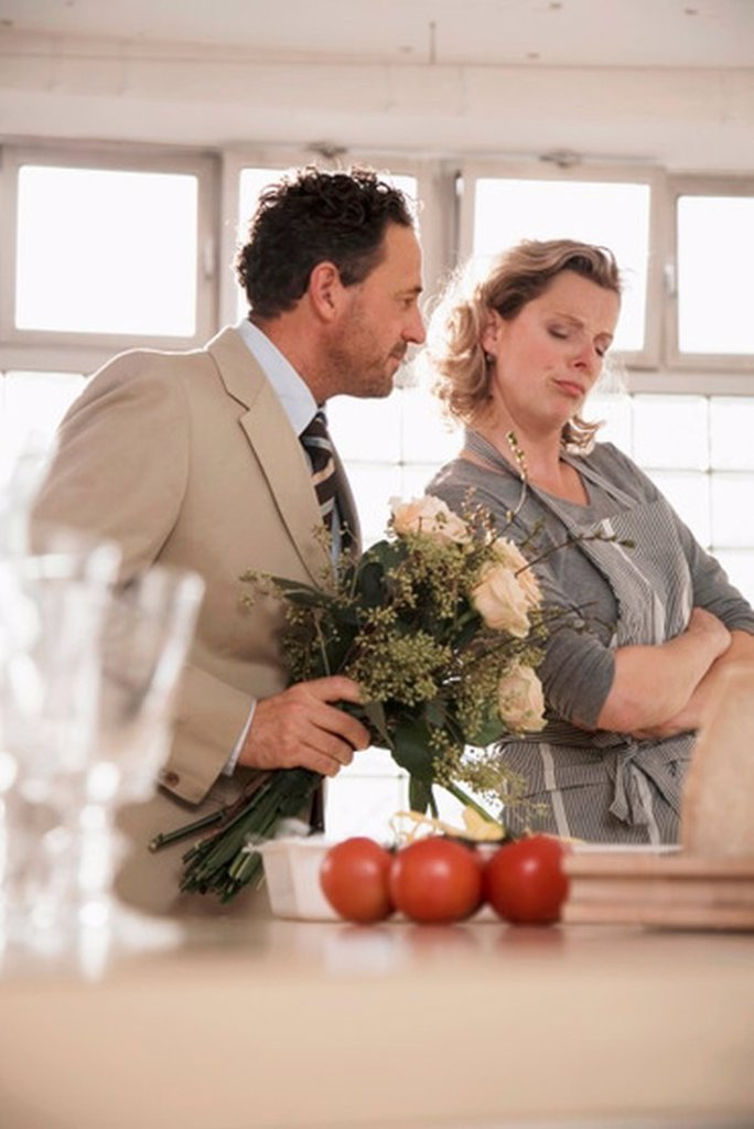 Mature couple in kitchen with flower bouquet : Stock Photo