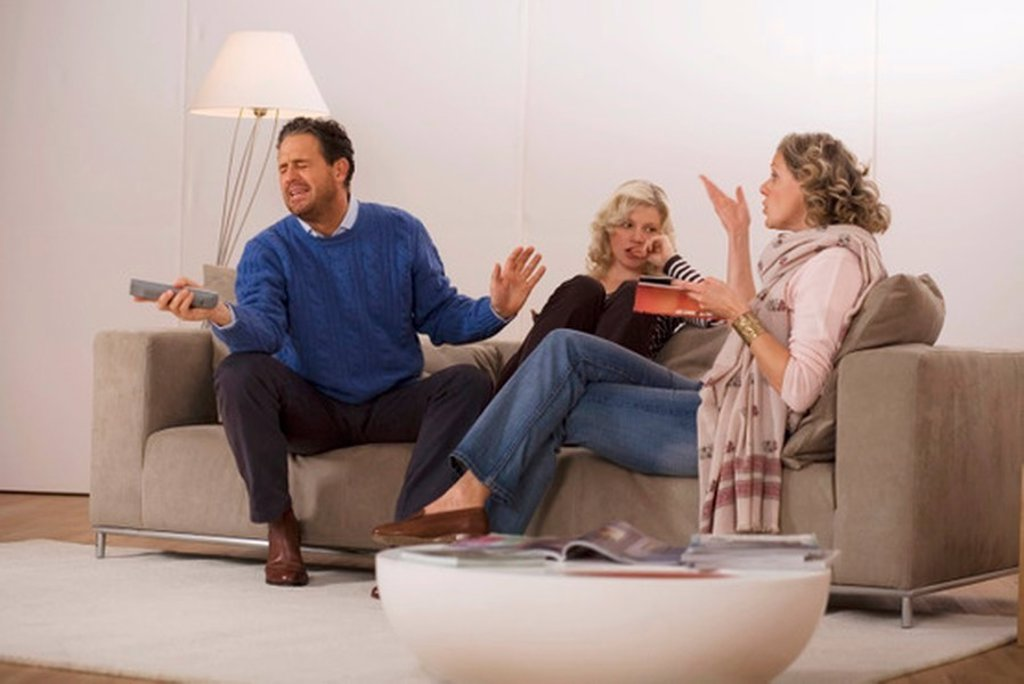 Stock Photo: 1815R-27172 Parents with daughter sitting on sofa in living room
