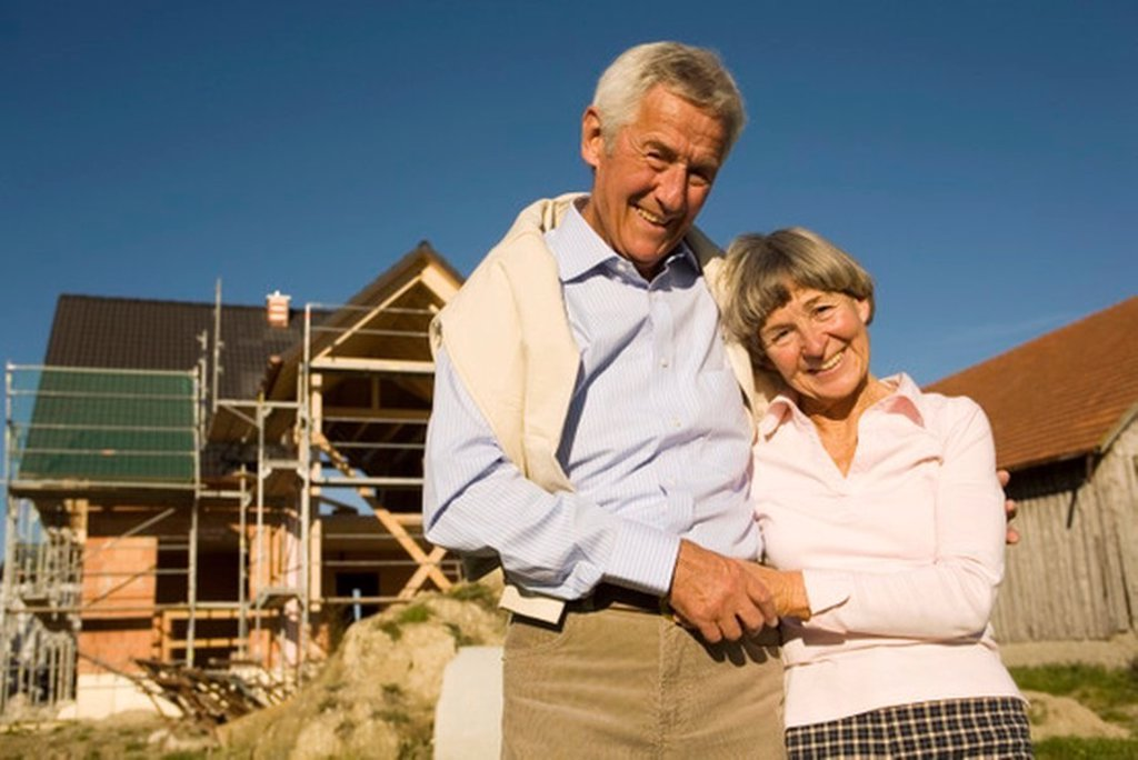 Senior couple in front of partially built house : Stock Photo