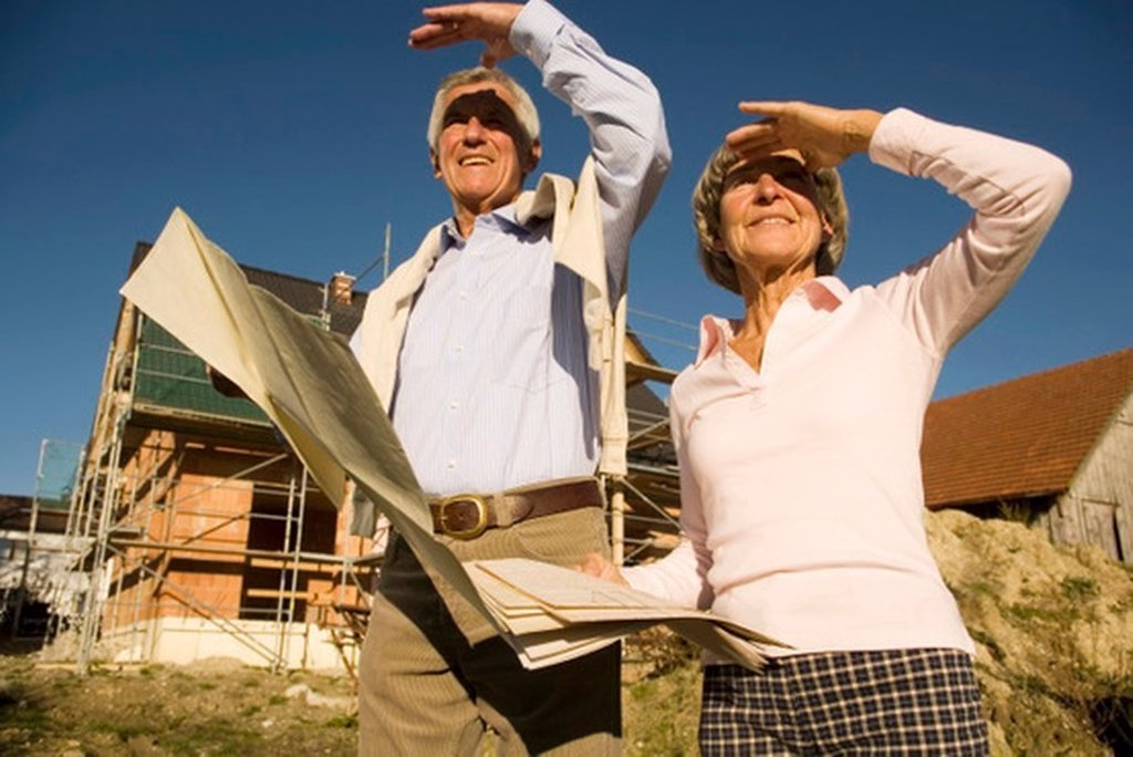 Stock Photo: 1815R-27301 Senior couple holding plan in front of partially built house
