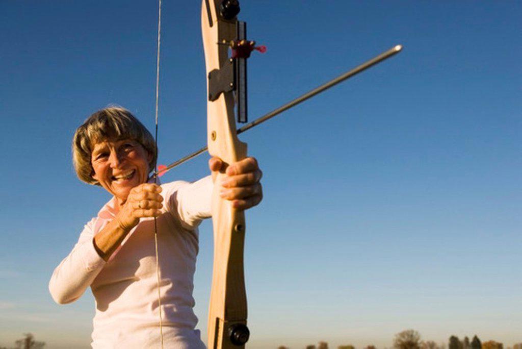 Stock Photo: 1815R-27312 Senior adult woman using bow and arrow