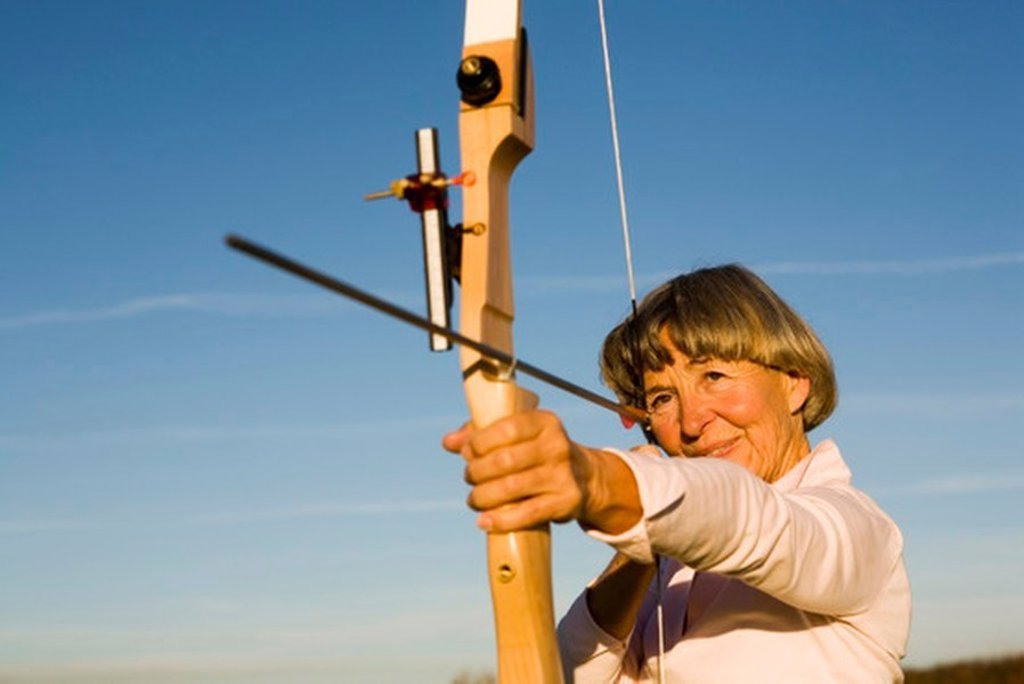 Senior adult woman using bow and arrow : Stock Photo