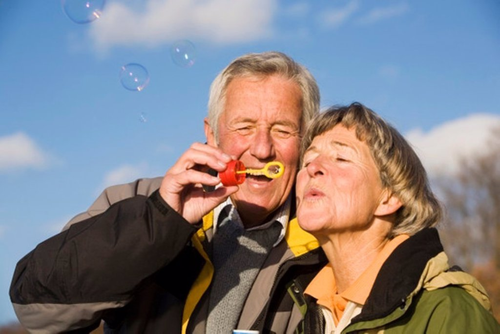 Stock Photo: 1815R-27343 Senior couple blowing bubble wand, close-up